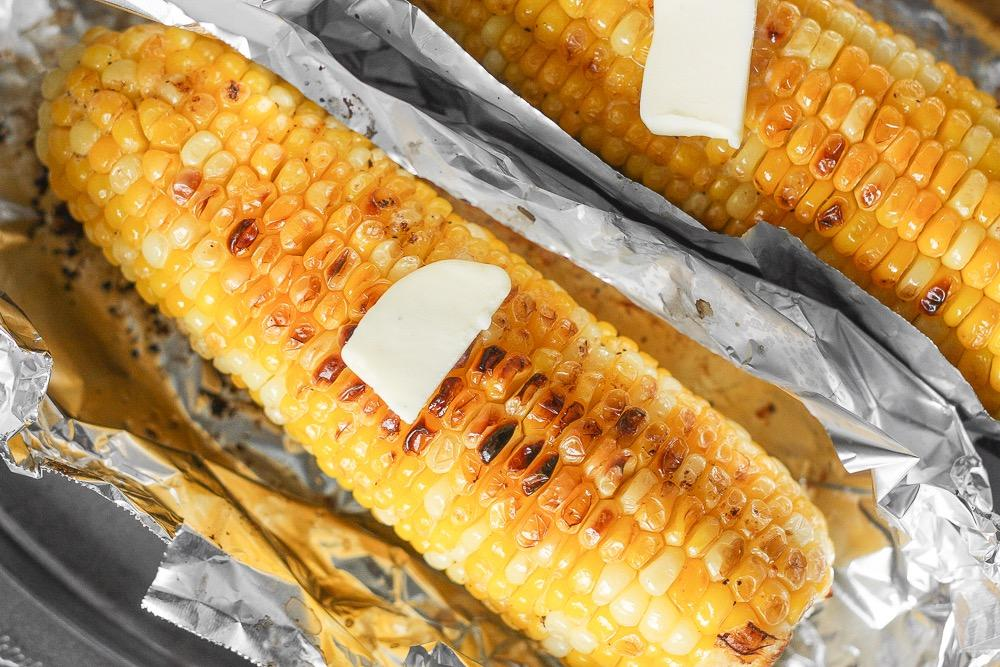 OVEN-ROASTED CORN ON THE COB 1/4 cup unsalted butter, softened 1 clove garlic, minced 1/4 teaspoon salt 1/8 teaspoon ground black pepper 4 cobs of corn, peeled 1. Preheat oven to 350 F. 2.