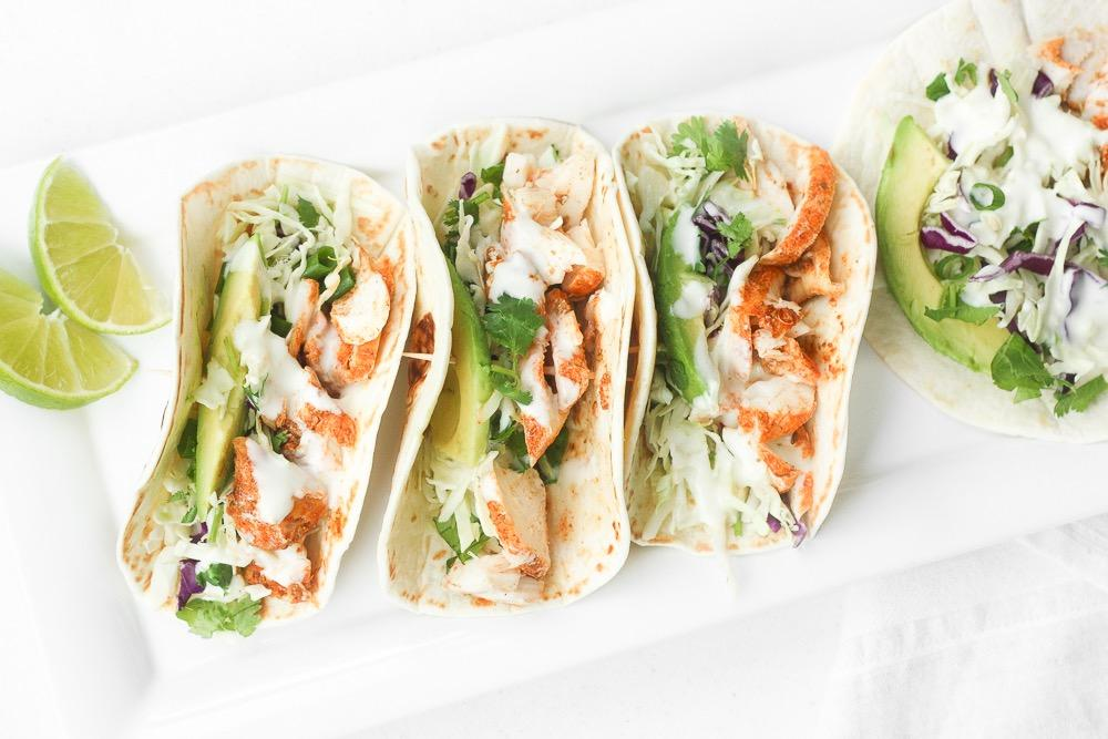 EASY FISH TACOS WITH LIME CREMA Lime Crema: 1/4 cup sour cream 3 tablespoons mayonnaise 1 tablespoon fresh lime juice zest from half a lime 1/4 teaspoon salt Slaw: 2 cups cabbage, shredded 1/4 cup