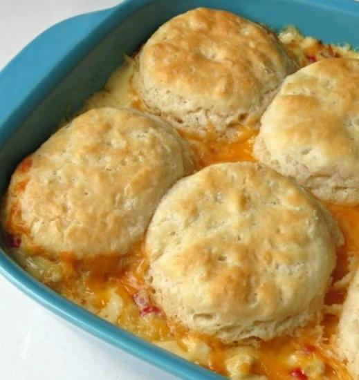 Chicken Biscuits Casserole 1 medium onion, chopped 1 1/2 teaspoons butter 4 cups Rotisserie chicken, chopped 1 small jar chopped pimiento 1 can cream of chicken soup 1 cup sour cream 1/2 cup milk 1