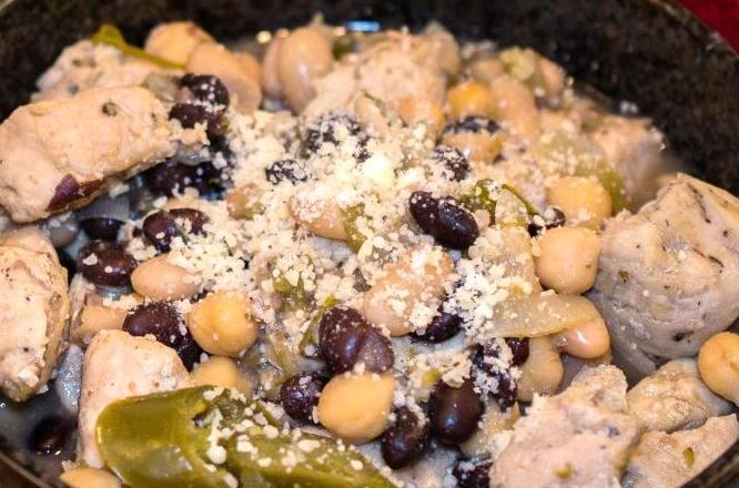 5 oz) can chicken broth 3 cups chopped cooked chicken breast 3 (15 oz) cans white beans (1 crushed) 1 can black beans 1 cup shredded Monterey Jack cheese Heat the oil in a large saucepan over